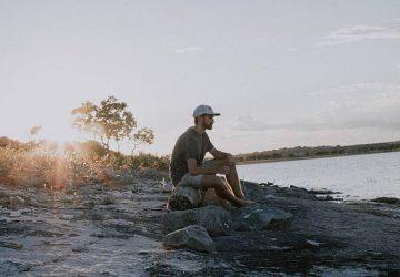 man sitting on rock beside water