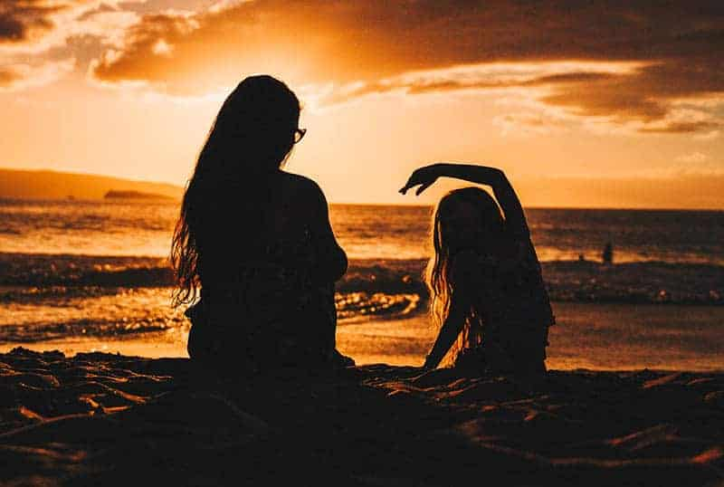 silhouette of mother and daughter on the beach