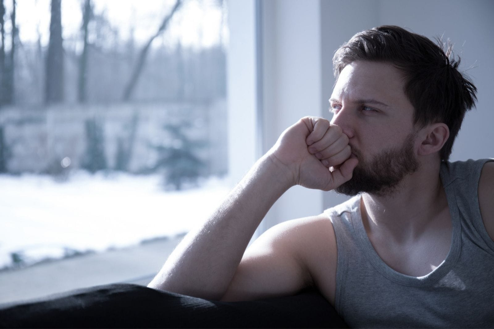 a man pensively looks out the window