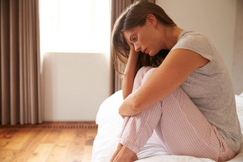 depressed woman sitting on the bed