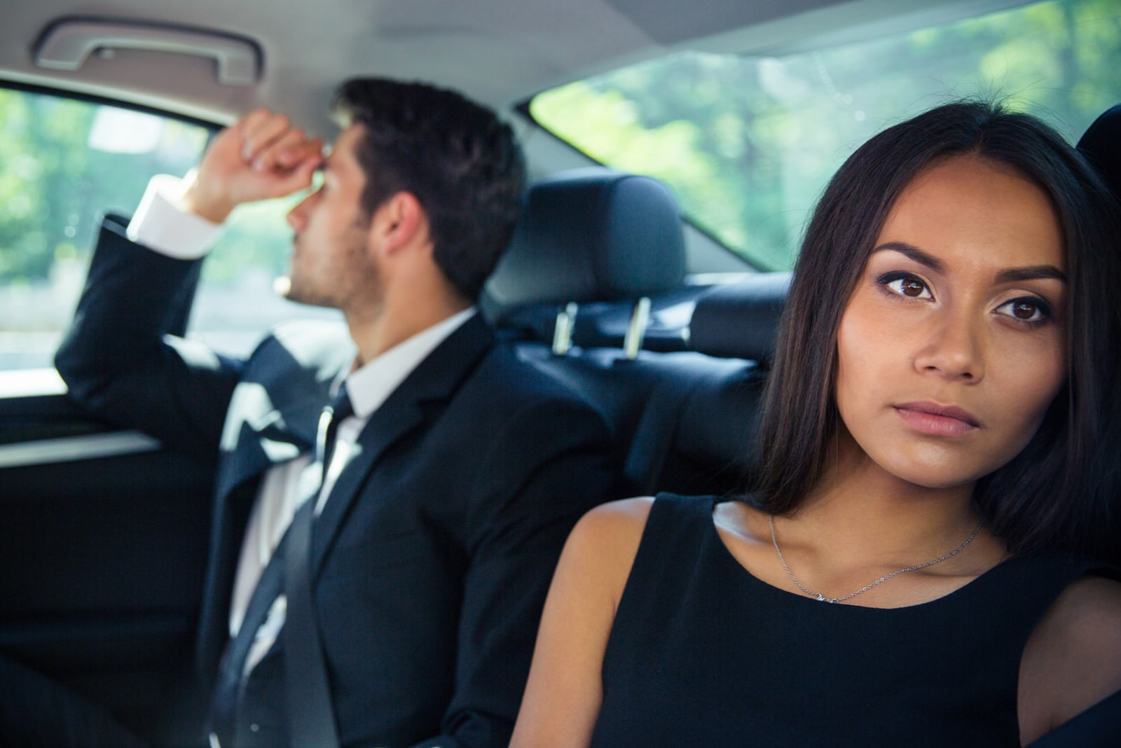 man and woman riding on back seat in car