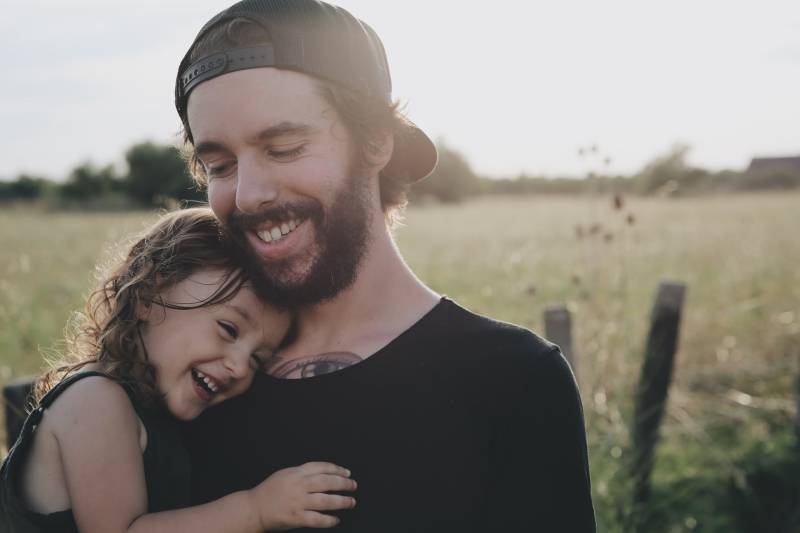 man carrying daughter in black t-hisrt outside
