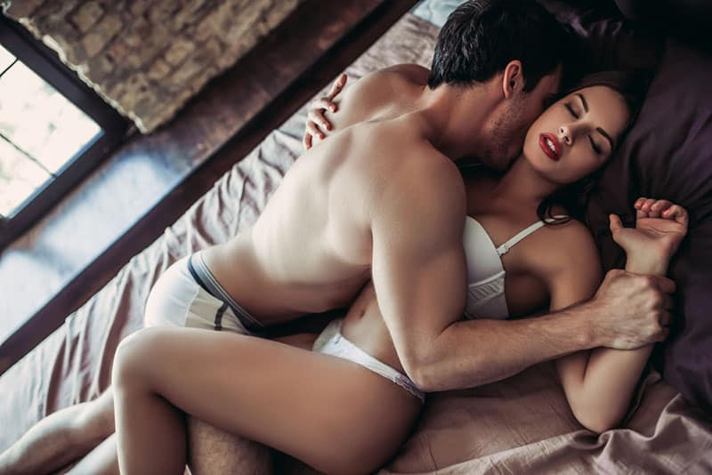 passionate man kissing woman in bed
