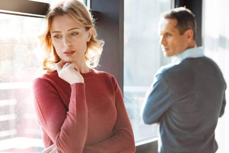 sad unhappy cheerless woman standing near her boyfriend