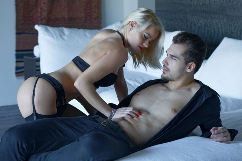 sexy woman in lingerie playing with man on bed