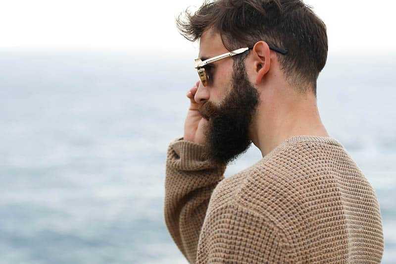 side view of bearded man wearing sunglasses and brown sweatshirt outside