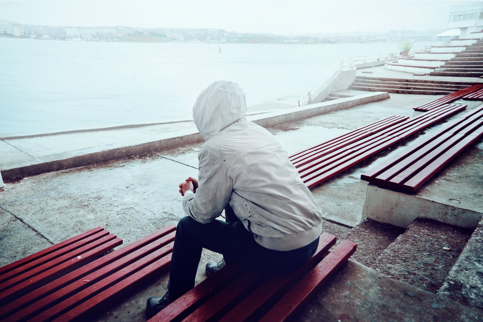 the man is sitting on a bench with his back turned