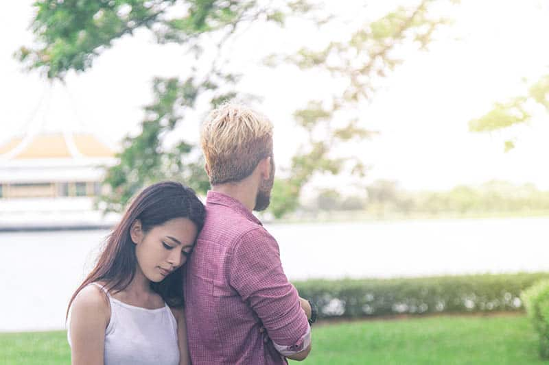 thoughtful woman puts head on man back while standing outside