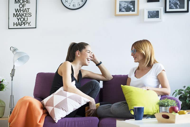 two women sitting on the couch and talking