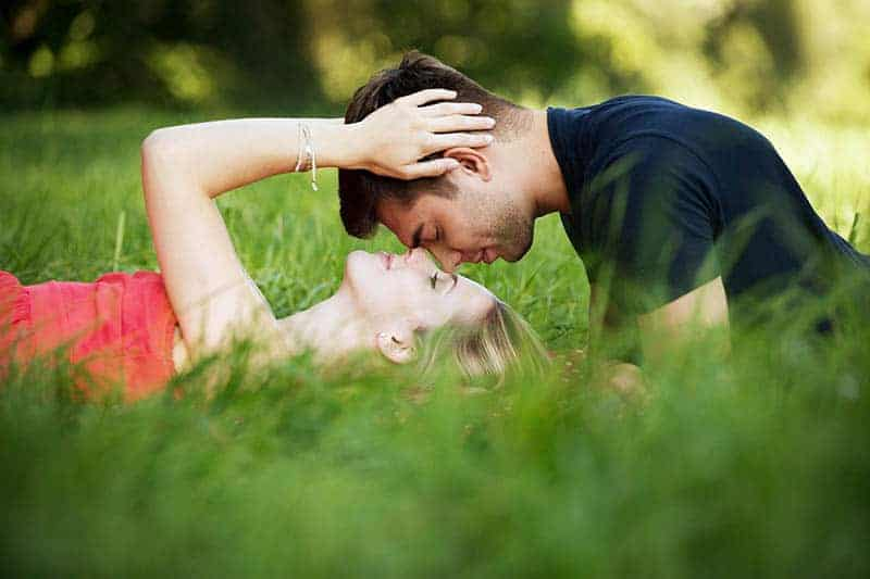 woman lying on grass field while man is over her face