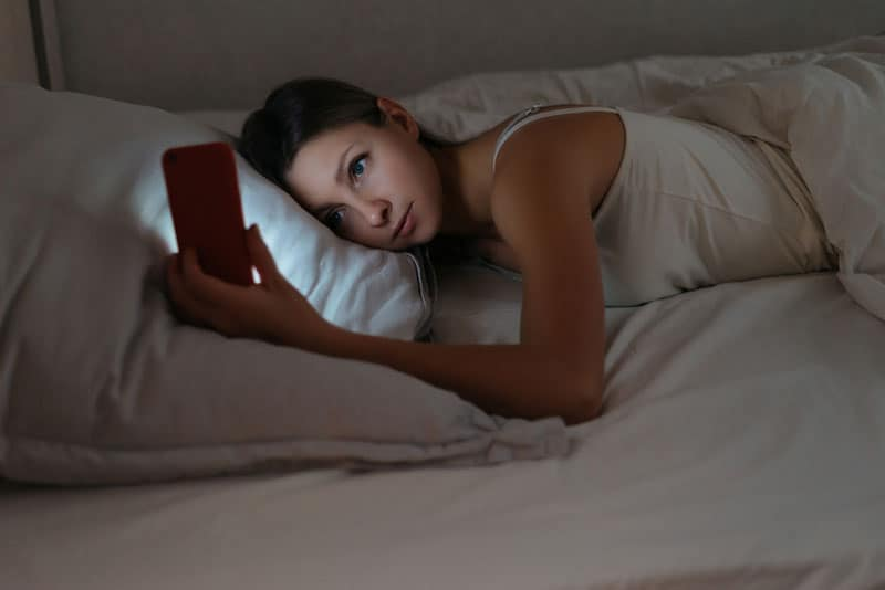 woman lying on white pillow and looking at her phone