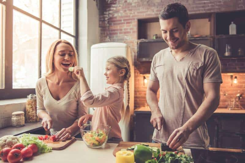 A pretty little girl and her parents-in-law cut vegetables and smile while cooking at home