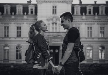 side view of smiling couple looking each other and holding hands