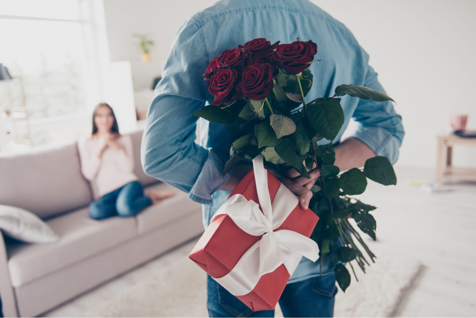 man surprising woman with flowers and gift