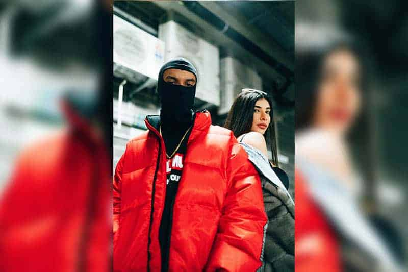 man wearing mask and red jacket standing beside woman