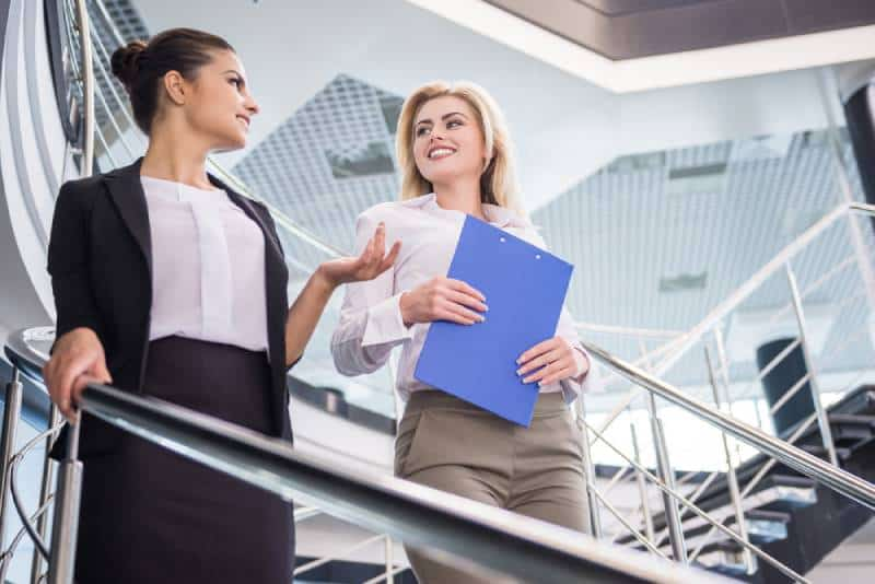 Two attractive business woman walking down the stairs and talking.