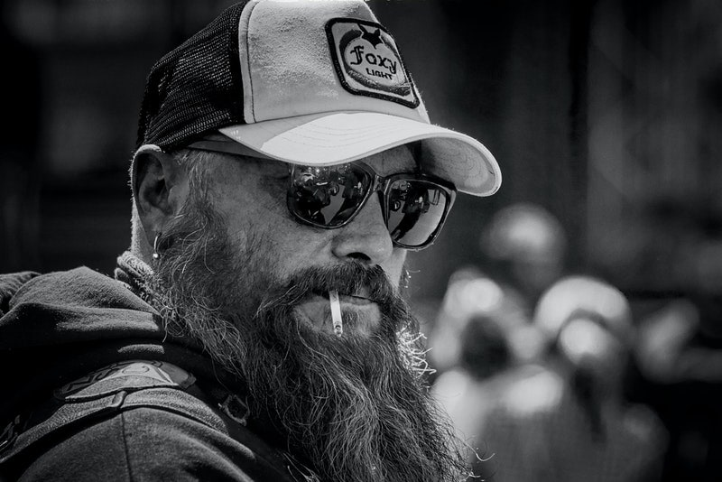 a man with a beard and a cigarette in his mouth