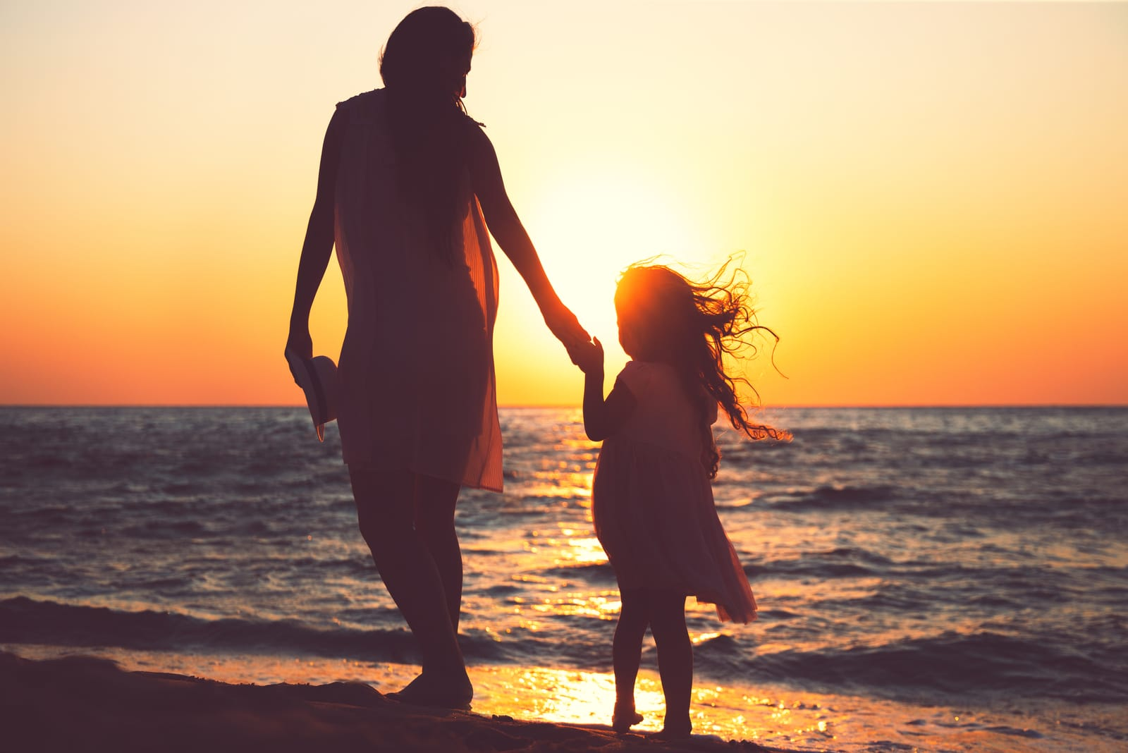 a woman walks the beach with a child