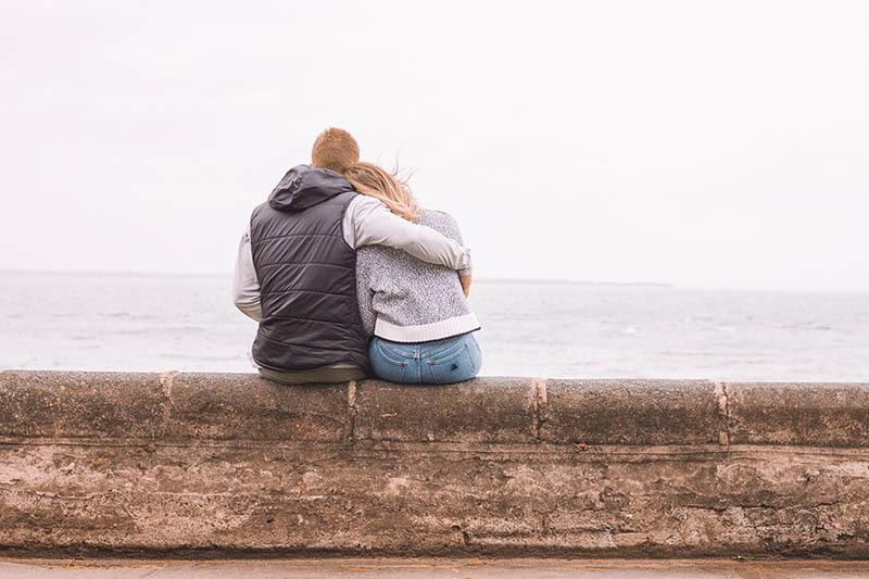 couple hugging in front of sea