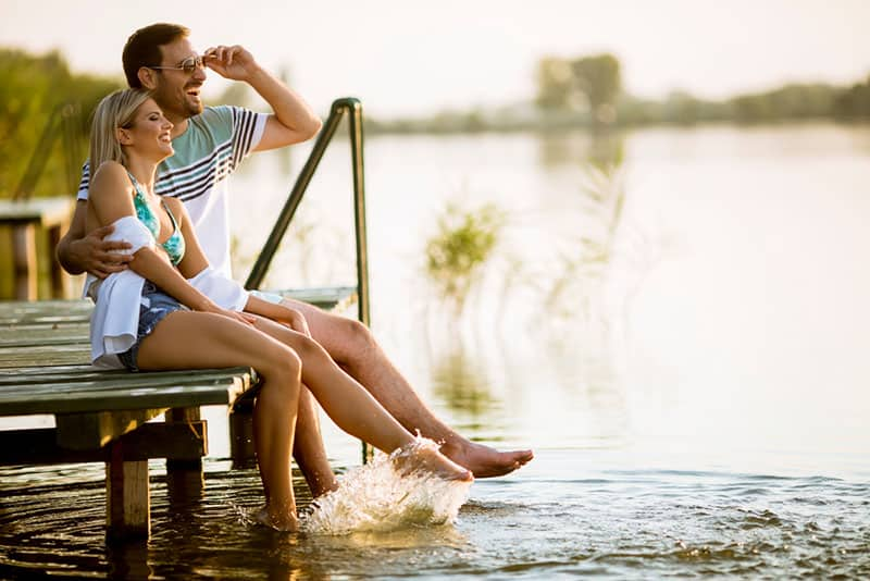 couple sitting on the pier by the lake