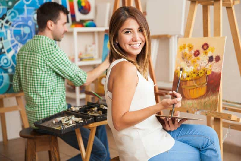 hispanic woman and man attending a paintih together