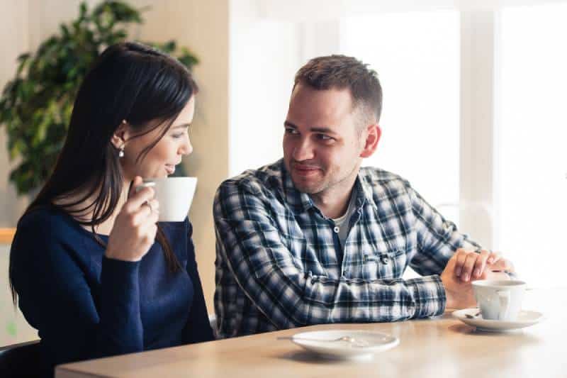 man and woman talking at cafe and drinking tea