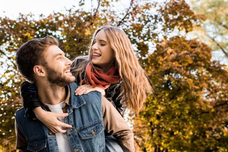 man piggybacking his smiling girlfriend in nature