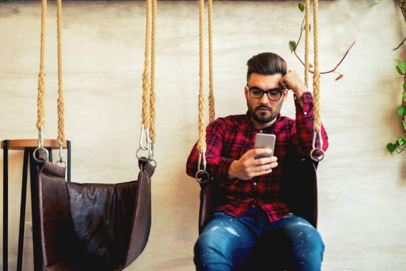 man typing on his phone and sitting on swing