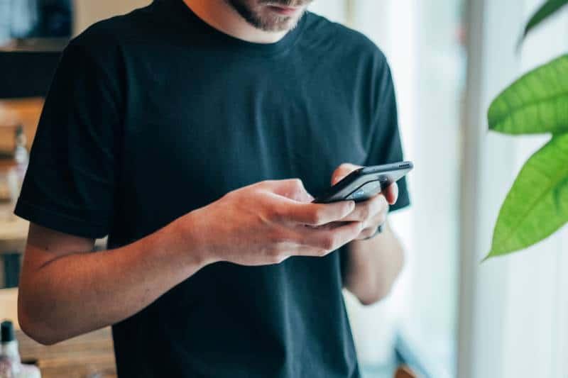 man typing phone at cafe