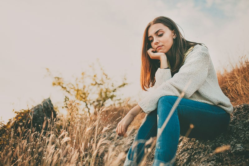 sad woman sitting in nature and thinking