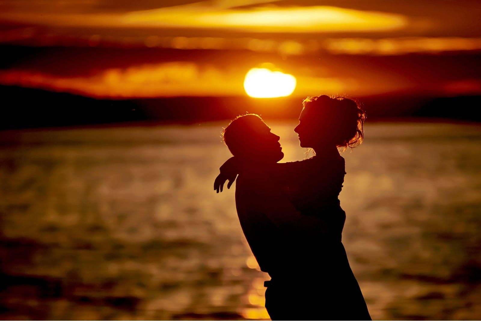 silhouette of couple hugging beside sea