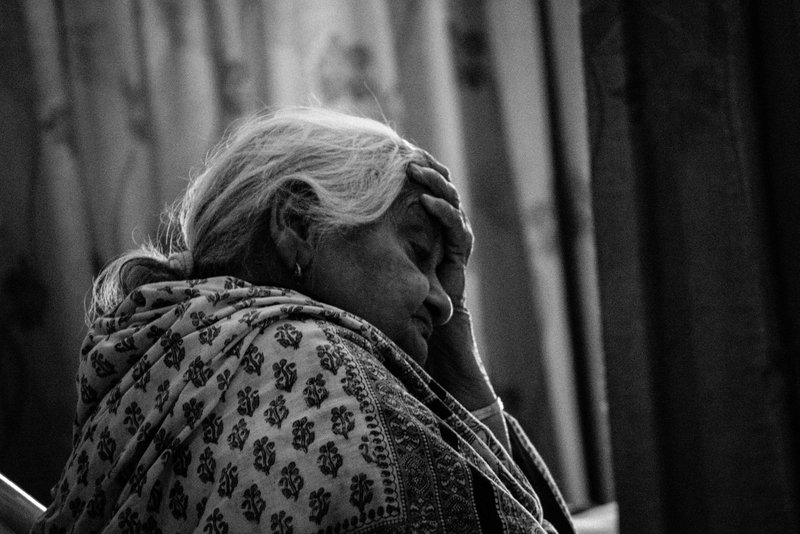 the sad old woman holds her head