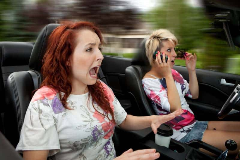 two females looks scary driving in car