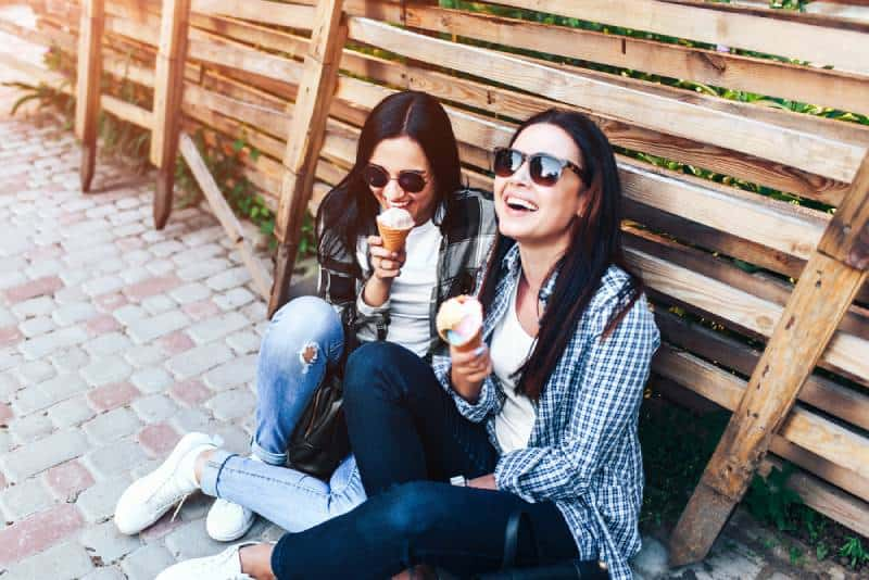 two smiling brunette girls eating ice cream outdoor
