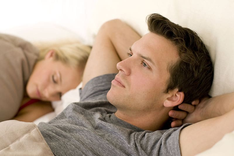 worried man in deep thoughts while woman sleeping