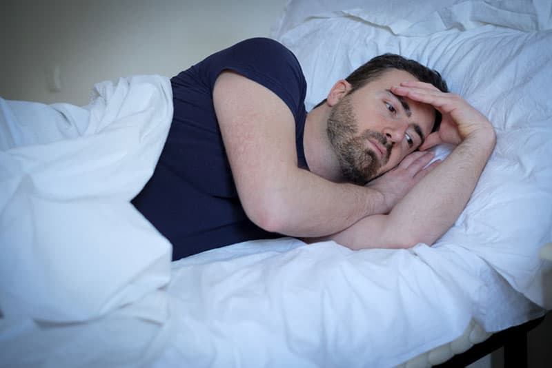 worried man laying in bed