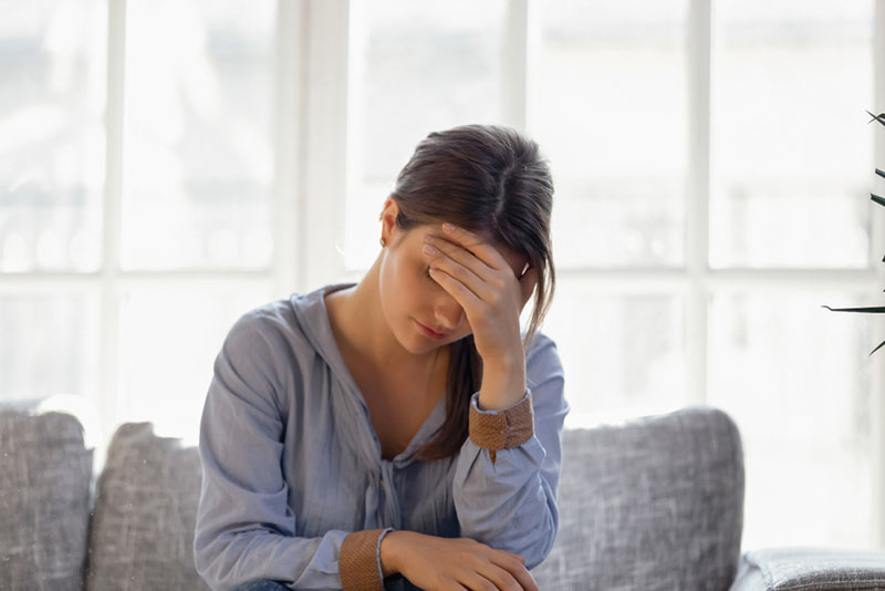 worried woman sitting on the couch