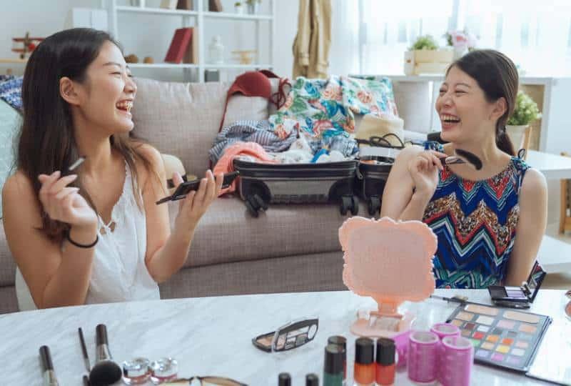 young asian woman putting makeup on