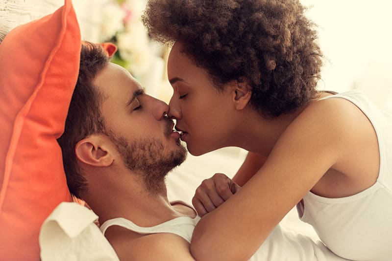 young couple kissing on the bed