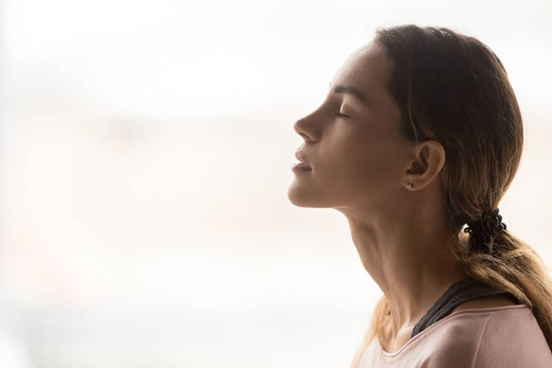 young woman taking deep breath