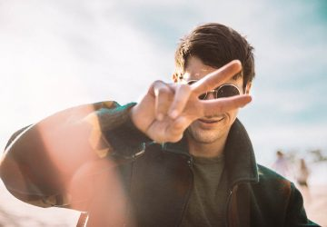 man gesturing peace sign outside
