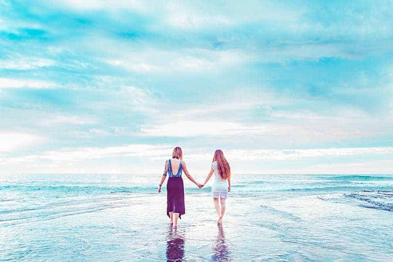 back view of two female friends holding hands while walking on the beach