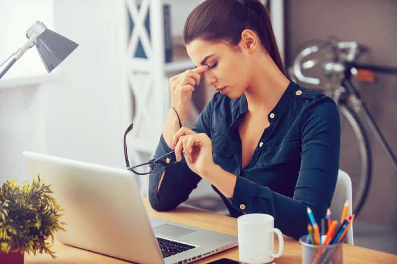 A frustrated young woman keeps her eyes closed as she sits at her workplace in the office