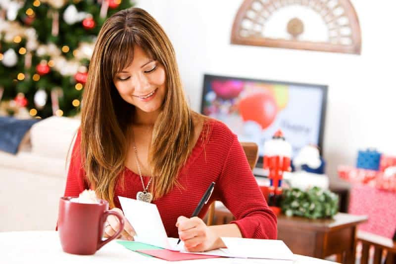 A woman who writes on cards and has cocoa