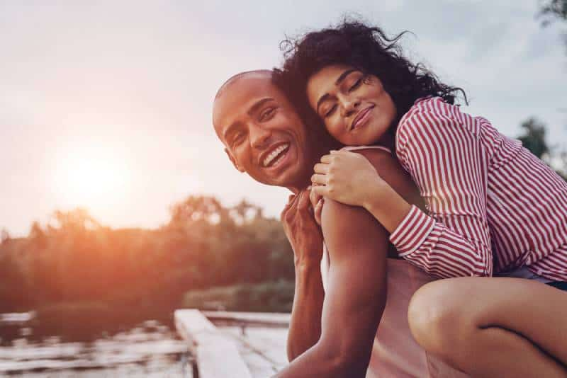 Happy young couple hugging and smiling while sitting near the lake