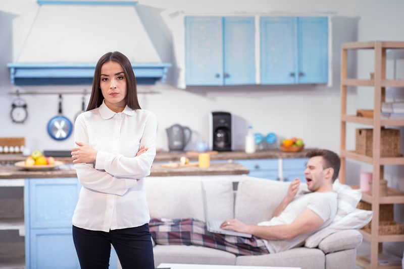 angry woman standing while lazy man laying on sofa