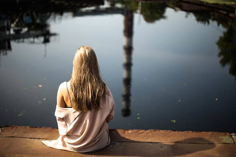back view of blonde female sitting on wooden dock in front of lake