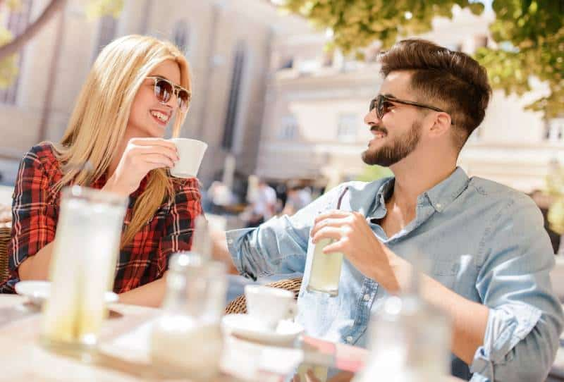 beautiful couple talking at cafe during daytime
