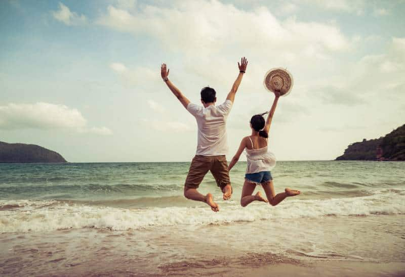couple jumping on the sand beach