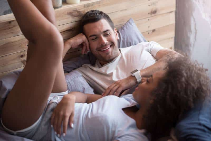 happy couple lying on bed and talking